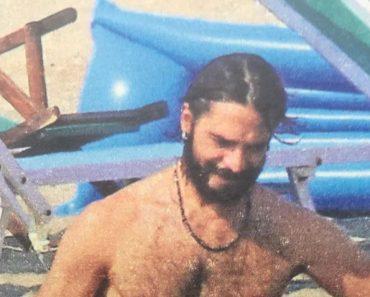 Marco Bocci in costume al mare con la famiglia e i capelli lunghi